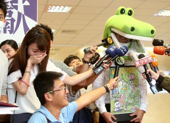國防部上午舉行記者會宣布一系列軍人節慶祝活動,參加活動的鱷魚先生受訪時,大家把麥克風放到鱷魚嘴巴裡,連女記者也忍不住笑場。記者邱德祥/攝影