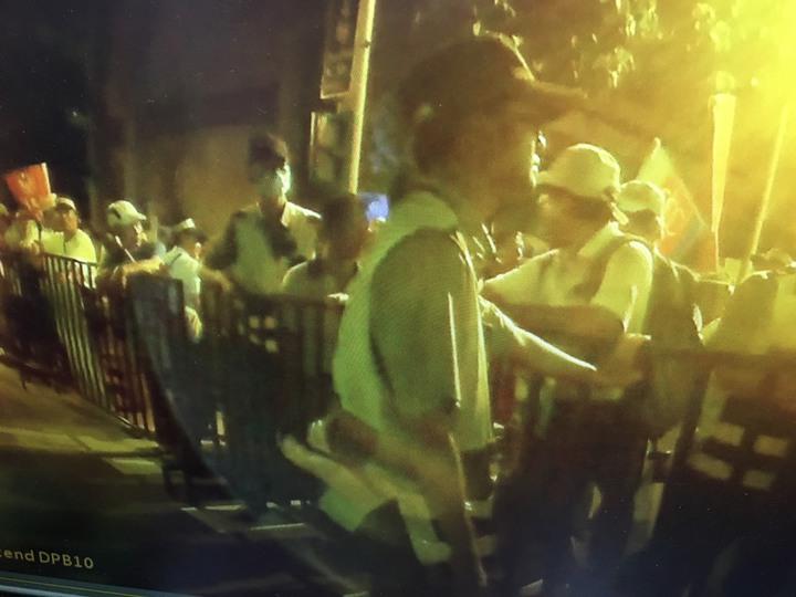 吳萬固推開鐵柵門讓群眾進去,員警人力不足只能眼睜睜看他們進去。記者蕭雅娟/翻攝