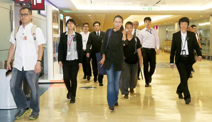 NGO工作者李明哲被大陸控訴涉嫌「顛覆國家政權罪」,李的妻子李凈瑜(中)前往大陸旁聽審判後,12日晚間搭機返抵桃園機場。  記者陳嘉寧/攝影