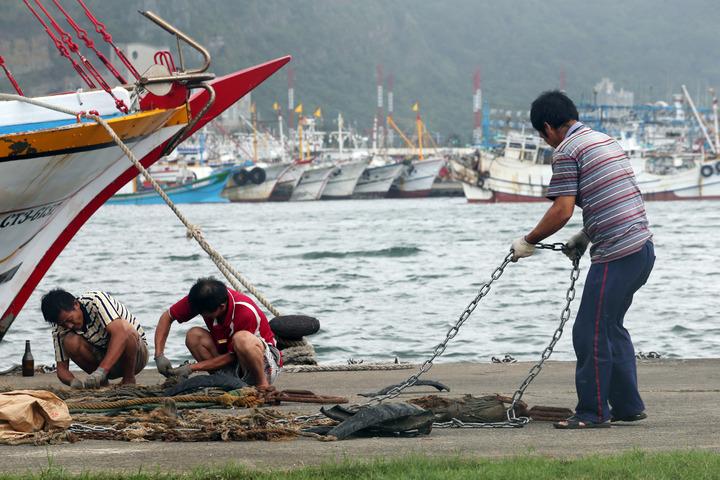 基隆八斗子魚港內停滿了躲颱風的漁船,船家用鐵鍊加緊牢固漁船,並利用靠港的空檔整理漁具。記者杜建重/攝影