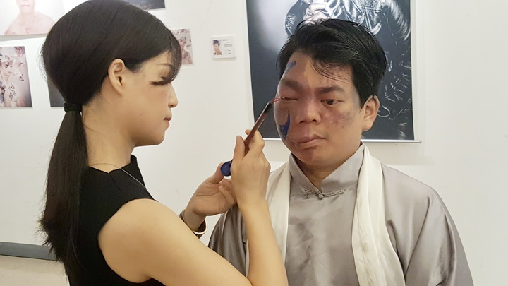 「破繭重生的美麗」攝影展上午在苗栗縣文化觀光局中興畫廊推出,模特兒之一的李兆翔現場接受彩妝師馬家駒的臉部彩繪示範。記者胡蓬生/攝影