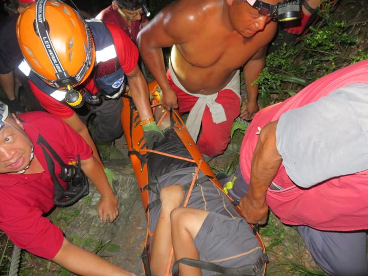 台東南橫栗松溫泉昨天1名許男受困,救難人員將他連拉帶拖,協助他脫困。圖/關山消防大隊提供