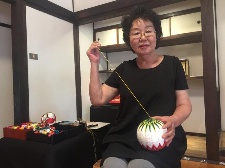 青木瀑布美老師示範彩線球製作。記者吳政修/攝影