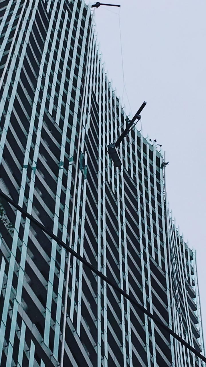 台中市42歲工人今天下午替大樓換裝玻璃時,因強風受困30樓半空中,最後幸運脫困。記者陳宏睿/翻攝