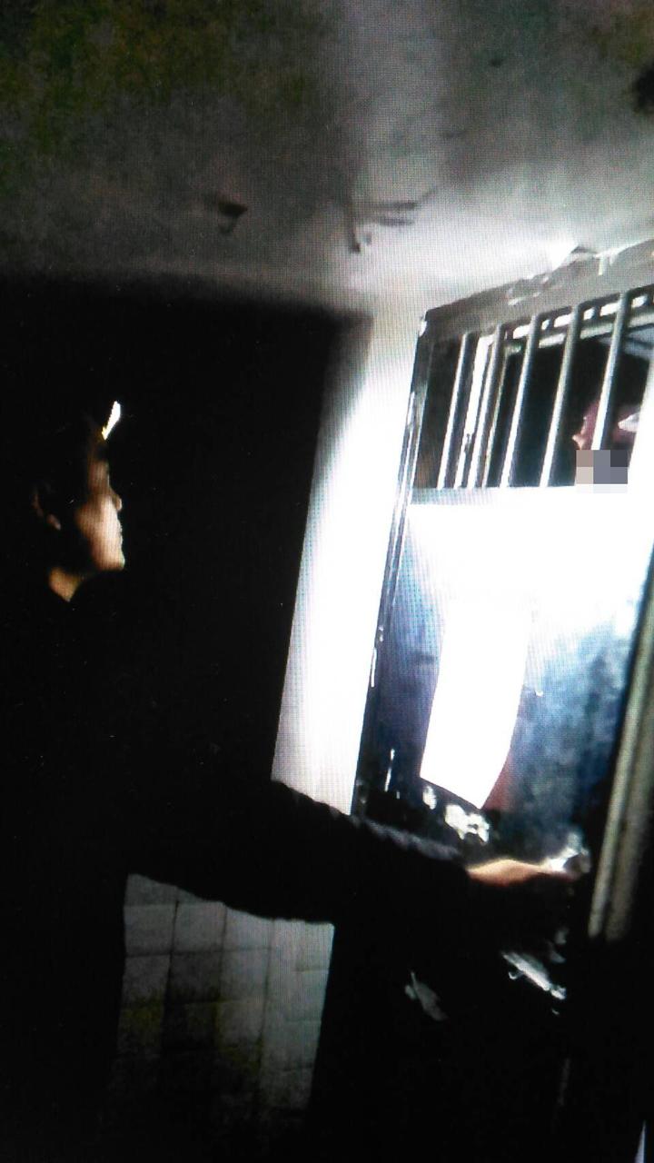 蔡姓通緝犯反鎖土地公廟廁所內,員警在外勸說。記者游明煌/翻攝