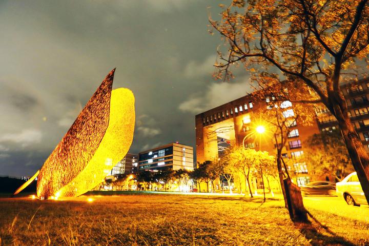 西班牙地景藝術家黃猴諾維亞(Juanjo Novella)為清華製作的巨型公共藝術品「葉子」(LEAF),夜間在燈光映照下,更顯風情綽約。圖/清大提供