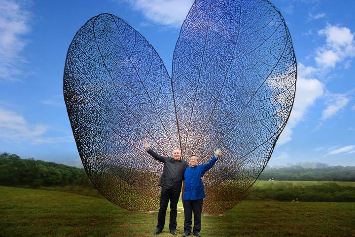 西班牙地景藝術家黃猴諾維亞(左)為清華製作的巨型公共藝術品「葉子」(LEAF),今天清華大學校長賀陳弘(右)為此揭幕。圖/清大提供