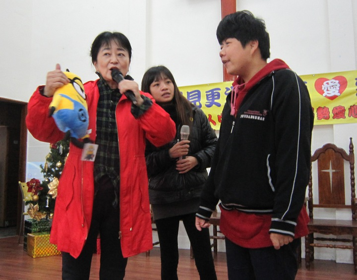 教誨師謝蕙芬(左1)主持有獎徵答,只要喜憨兒答對她手中的布娃娃名字,就是他的耶誕禮物。記者何烱榮/攝影