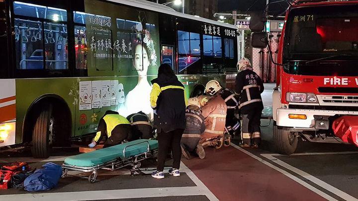 女騎士被捲進公車底下,消防隊員正在協助脫困。 圖/翻攝爆料公社