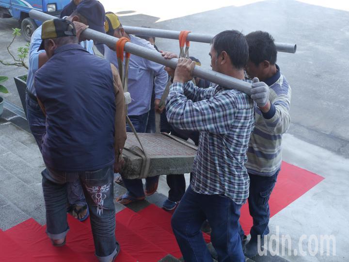 百年石碑噸位不輕,多名壯丁合力遷移步上紅毯進入震威宮。記者徐白櫻/攝影