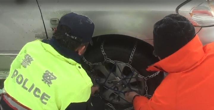 合歡山雪季勤務員警幫雪鍊鬆脫的車輪重新綁緊。圖/警方提供