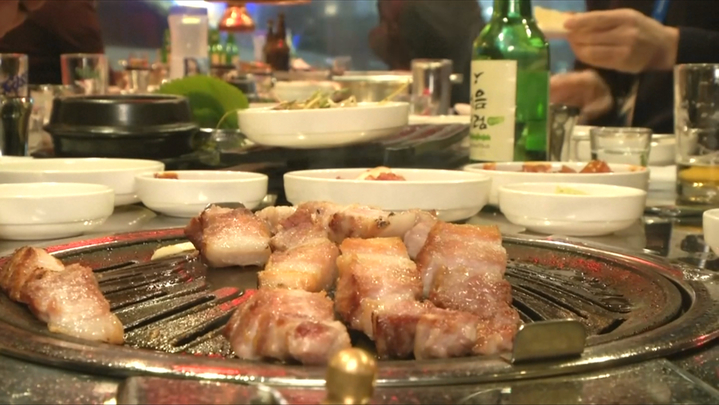 韓式燒酒搭配鹽烤豬五花肉,是遊韓必吃料理之一。路透