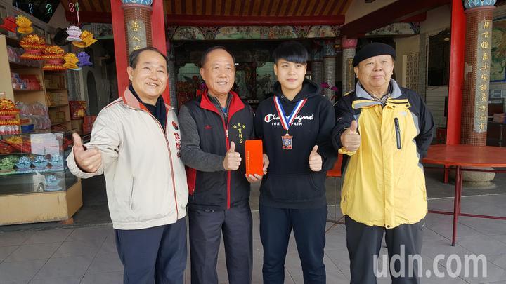 去年從後龍國中畢業的安珮帆(右二)在美國跆拳道公開賽榮獲銅牌,後龍萬善祠百姓公管委會主委李長峰(左二)等人今天特別頒獎勉勵。記者胡蓬生/攝影