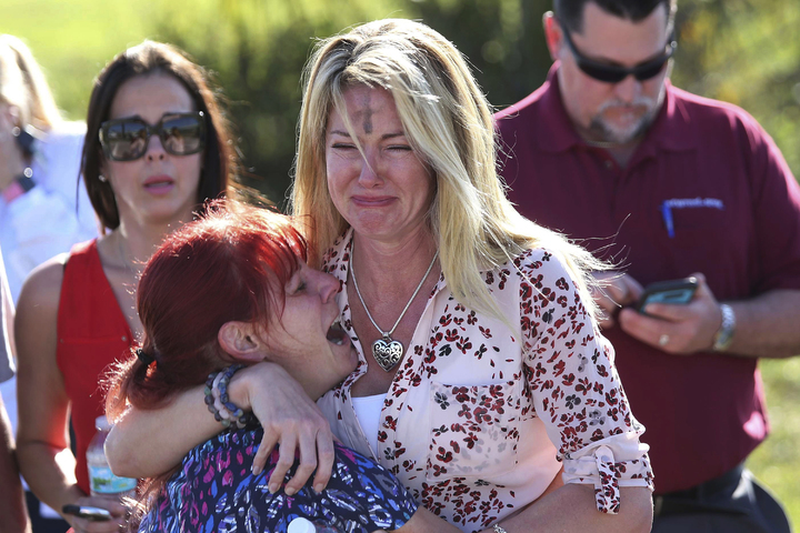 美國佛羅里達州一所中學驚傳校園槍擊事件,消息傳出後,家長焦急在外等待,槍手為一名遭到退學的19歲學生,當地時間14日下午,他持槍返校展開掃射,奪走至少17條人命。圖片/美聯社