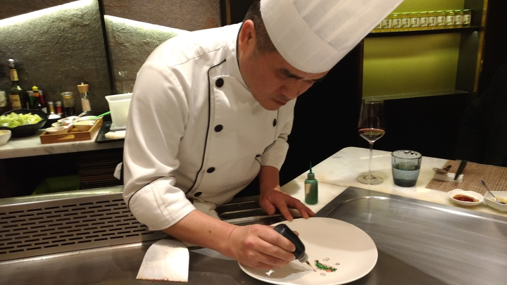 台中市的鐵板燒廚師王顗荃用沾醬在盤上作畫,為台灣和花蓮災民祈福。記者黃寅/攝影