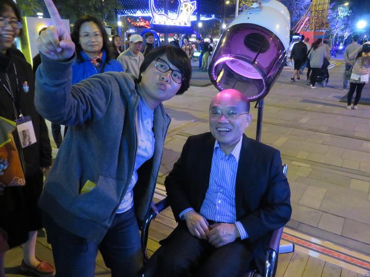 行政院前院長蘇貞昌(右)觀賞小女兒蘇巧純(左)設計的235大樂園,坐在美髮椅燈具上聆聽女兒導覽解說。記者魯永明/攝影