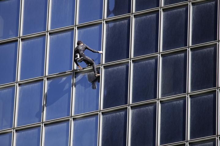 「法國蜘蛛人」羅伯特,14日挑戰187公尺高的道達爾大樓,1個多小時後成功登頂。美聯