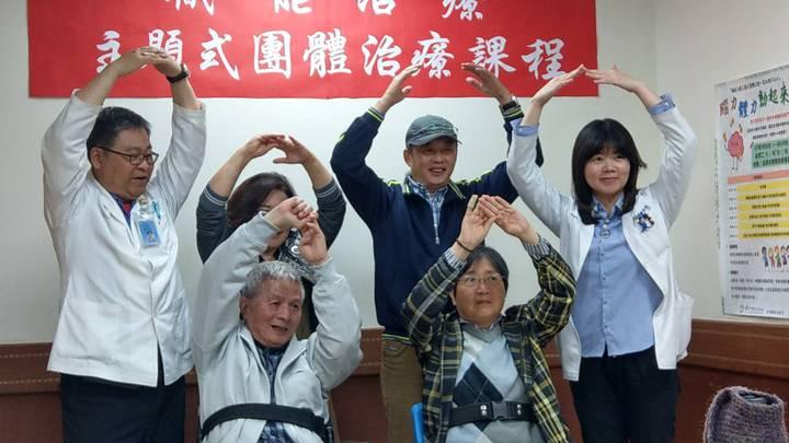 蔡秀盡(前排右)、王桂崇(前排左)經接受主題式團體治療課程後,可配合「心花開」音樂比動作。記者趙容萱/攝影