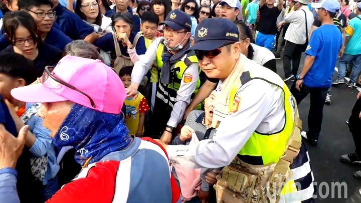 一位孝心民眾推著輪椅,上面坐著高齡90歲的輕微失智老父親,在眾人協力下完成鑽轎底的心願。記者黑中亮/翻攝