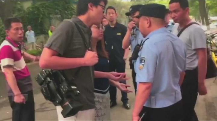 香港Now新聞攝影記者徐駿銘(左二)與記者李彤茵與警方就採訪證件被扣發生爭執。美聯