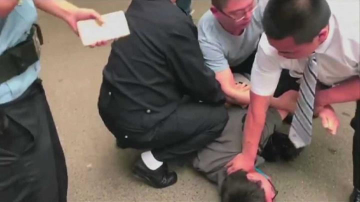 香港Now新聞攝影記者徐駿銘被北京的便衣刑警強押在地,隨後被上銬與押入警車帶走。美聯