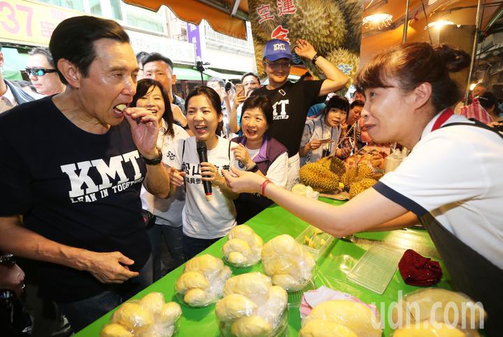 前總統馬英九(左一)上午陪同國民黨台北市議員參選人徐巧芯(左三)前往吳興市場掃街拜票,受到市場內婆婆媽媽的熱烈歡迎,還一口吃下水果攤商送上的榴蓮。記者胡經周/攝影