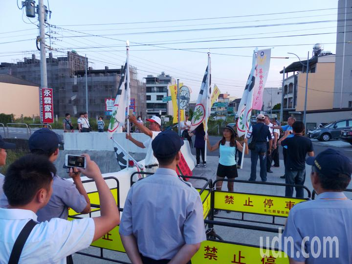 陳抗人士扛著抗議布旗,遭警方阻隔在距離員林演藝廳數百公尺之外。記者凌筠婷/攝影