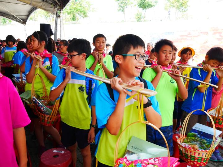 學童在客家成長禮活動中開心地挑擔,象徵傳承客家先民精神,肩負責任耕耘豐富人生。圖/客家文化發展中心提供