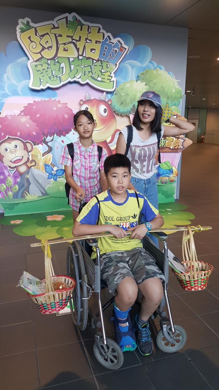 新北市大觀國小學童賴昱銓腳受傷,仍開心地坐輪椅到台灣客家文化館參加成年禮活動。記者胡蓬生/攝影