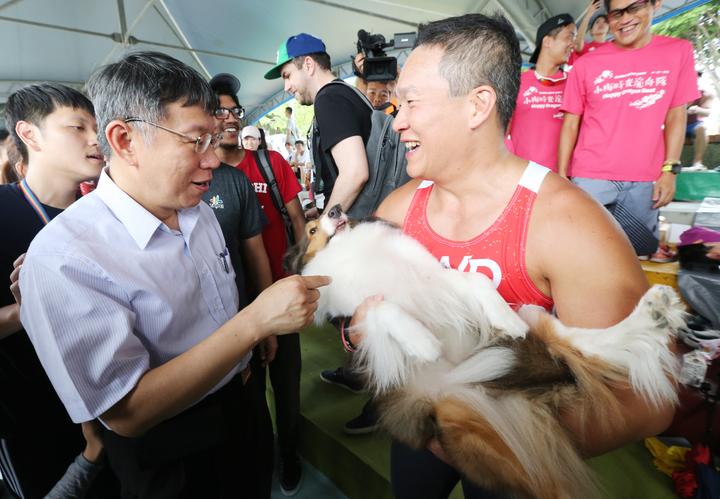 台北市長柯文哲(左)下午前往大佳河濱公園,參與端午節系列活動,他沿河岸探訪龍舟賽選手,一路受到選手熱烈歡迎,一名鐵粉帶著狗來拍照,直說自己與狗都是鐵粉。記者許正宏/攝影