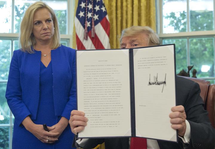 美國總統川普20日在白宮高舉停止拆散非法入境移民家庭的行政命令給媒體拍照,左為國土安全部長尼爾森。美聯