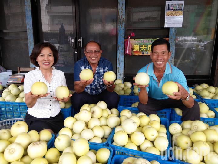 宜蘭壯圍鄉小農陳渭川(右)栽種的蜜香瓜,在台北果菜批發市場拍出每公斤290元高價,農會理事長林听洲(中)大讚好吃。記者戴永華/攝影
