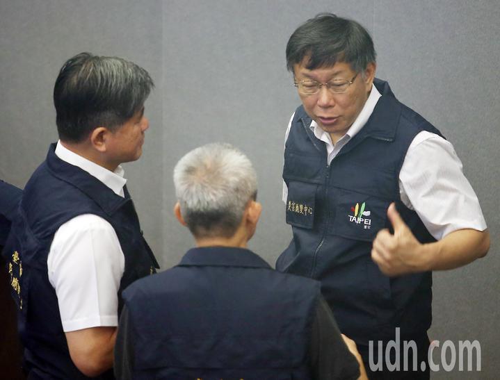 台北市長柯文哲(右)上午巡視台北市災害應變中心,在開會前與幕僚再次確認颱風的動態。記者杜建重/攝影