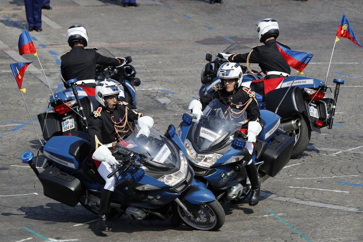 法國國慶日閱兵,儀隊重機車隊花式表演也出包,兩台重機對撞摔跤,好尷尬。美聯社