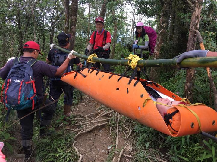 消防救護人員讓傷者躺在軟式擔架裡,用竹竿吊起擔架把傷者運下山。   圖/消防局提供