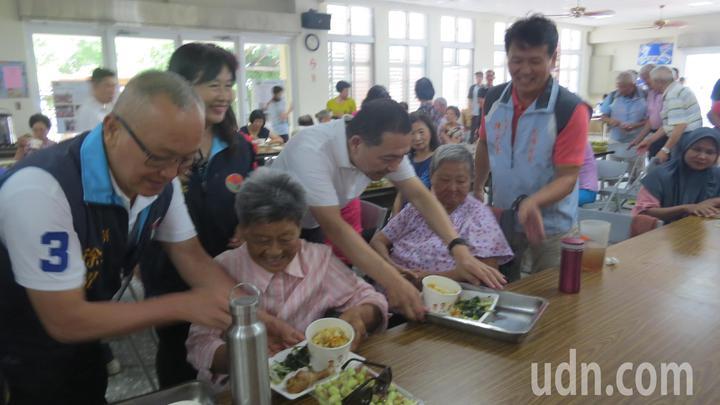 苗栗縣長徐耀昌(左一)及新北市長參選人侯友宜(右端餐盤者)今天到仁安社區與老人共餐,並幫忙送餐盤。記者范榮達/攝影