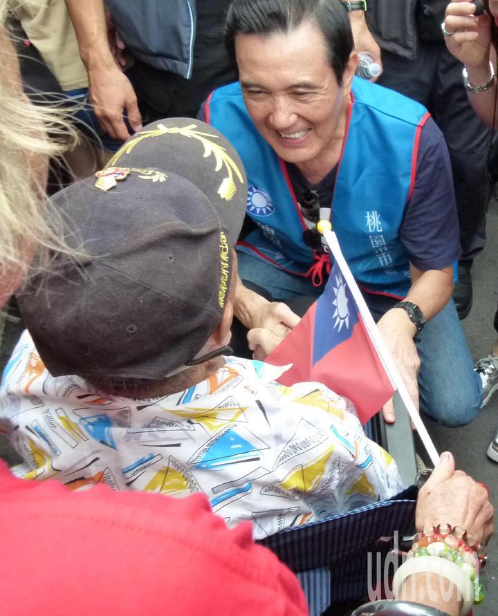 百歲人瑞擠在人群中,馬英九彎下身向老榮民致意。記者鄭國樑/攝影
