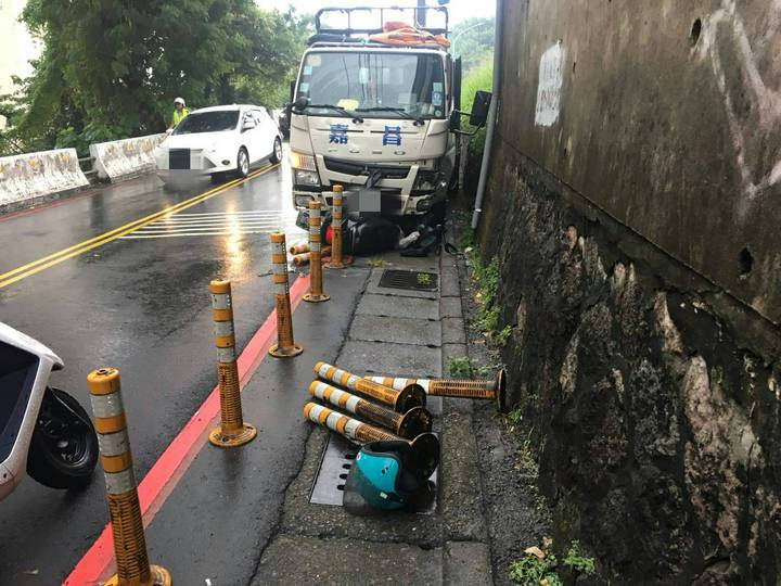 車禍位置在淡大校門口附近,貨車失控衝向山壁撞上停等紅燈的機車。記者林昭彰/翻攝