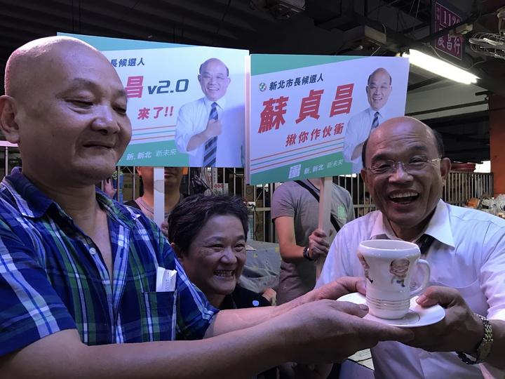 民進黨新北市長參選人蘇貞昌清晨到三重果菜市場拜票,有攤商拿出十多年前獲贈印有蘇貞昌漫畫圖案的杯子。記者陳珮琦/攝影