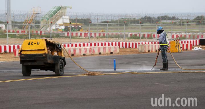 桃園機場第3航廈計畫中最重要的WC滑行道西移工程,W2滑行道15日全部完工,預計16日中午正式啟用。圖為工程人員15日正進行滑行道最後的整理。記者陳嘉寧/攝影