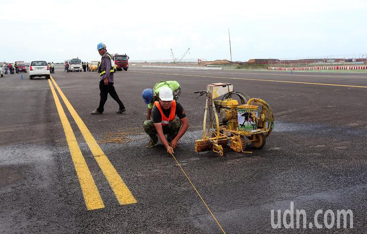 桃園機場第3航廈計畫中最重要的WC滑行道西移工程,W2滑行道15日全部完工,預計16日中午正式啟用。圖為工程人員15日正進行滑行道最後的標線繪製。記者陳嘉寧/攝影