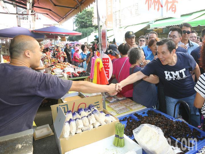 前總統馬英九(右)前往水湳市場掃街拜票時與熱情民眾握手。記者黃仲裕/攝影