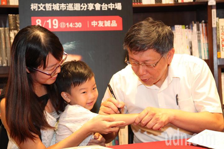 台北市長柯文哲下午到台中市中友百貨的誠品書店舉辦「光榮城市」一書的城市巡迴分享會,一位媽媽帶著3歲兒子讓柯在手臂上簽名。記者黃寅/攝影