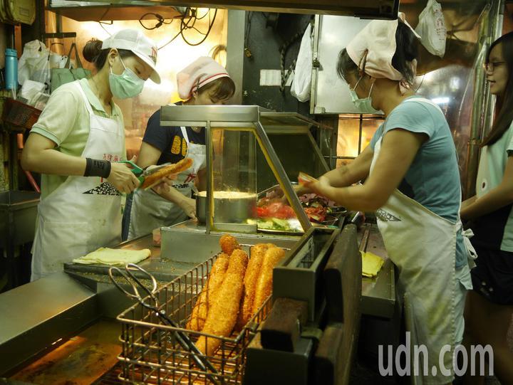 暖男陳恩在廟口夜市,幫客人買美食。記者吳淑君/攝影