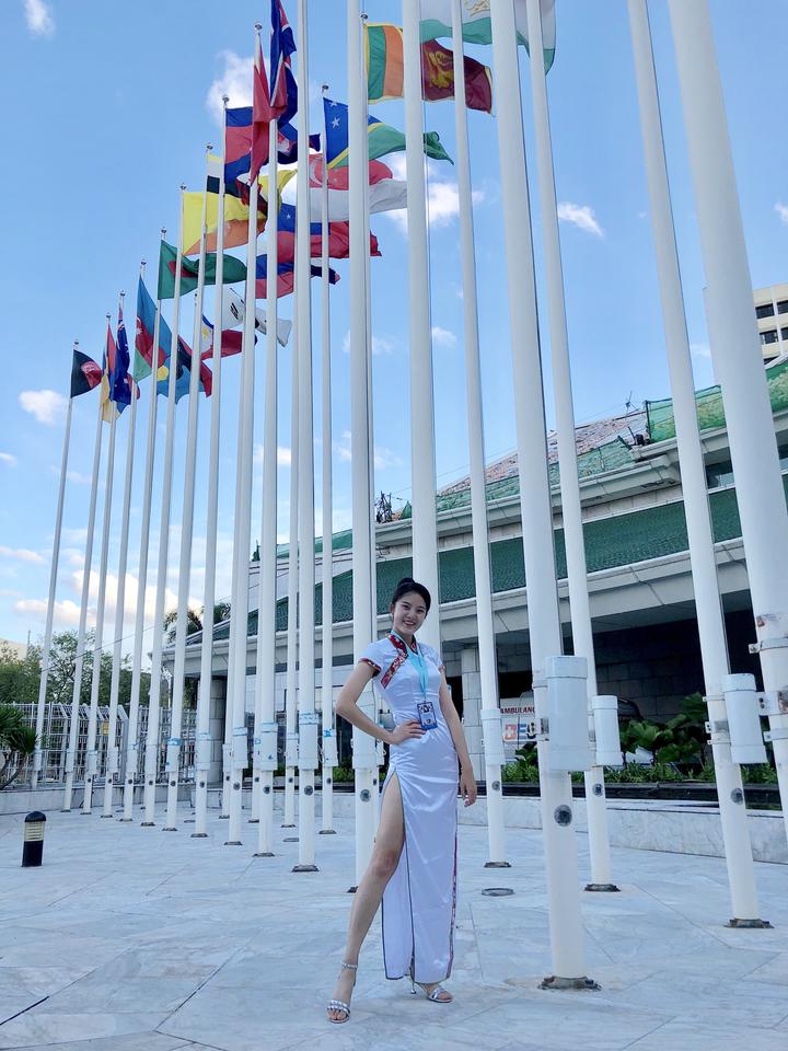 國立清華大學科管所學生邱怡澍穿上客家花紋的旗袍,向各國代表多介紹台灣。圖/清大提供