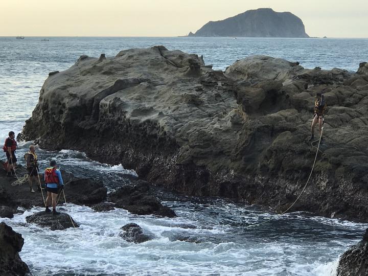 為剪斷釣客任意釘上的橫渡繩索,新北消防局瑞芳分隊今出動4員,綁上繩索、跳下海游到對岸,再攀爬五公尺高岩壁,利用電鋸切除鋼釘、繩索,十分危險。圖/瑞芳區長陳奇正提供