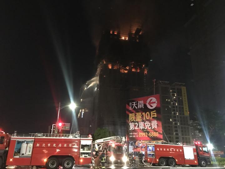 新北市新莊區中央路736號對面工地24樓建築物的15、16樓全面燃燒,且向上延燒,消防局架設雲梯車灑水灌救。記者袁志豪/攝影
