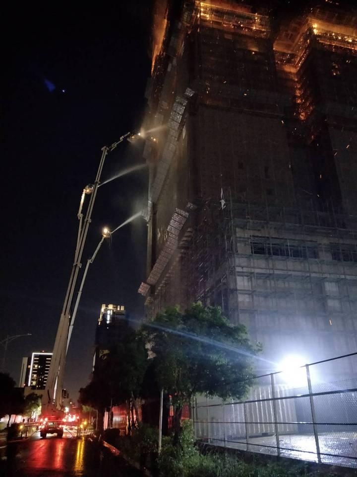 新北市新莊區中央路736號對面工地24樓建築物的15、16樓全面燃燒,且向上延燒,消防局架設雲梯車灑水灌救。記者袁志豪/翻攝
