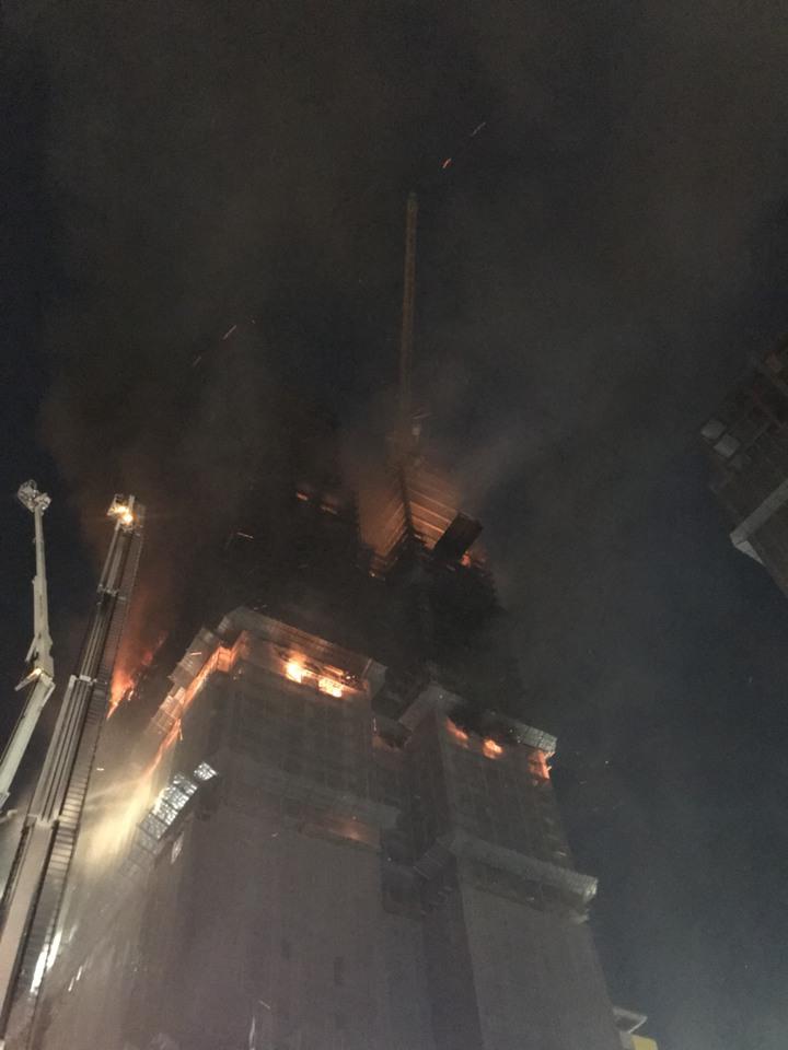 頂樓上方有一高聳吊臂,警消都在觀察是否會因火勢而掉落。記者袁志豪/攝影