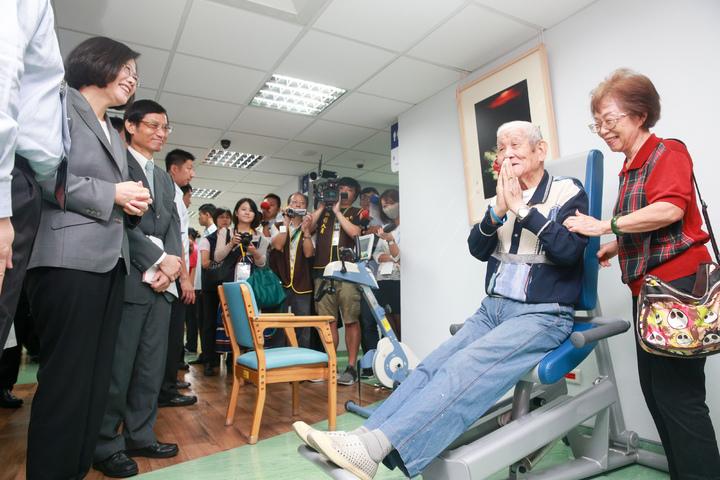 蔡英文總統(左一)上午在台北榮民總醫院日間照顧中心,出席「全人創新日照暨長照推動成果展」,在工作人員的解說下參觀長者使用復健器材。記者林伯東/攝影